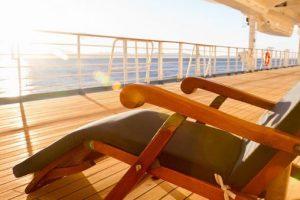 Deck chair in setting sun on cruise ship
