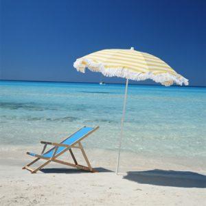 Deckchair under umbrella on deserted tropical beach