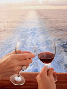 Toasting with 2 glasses wine as cruise ship sails away